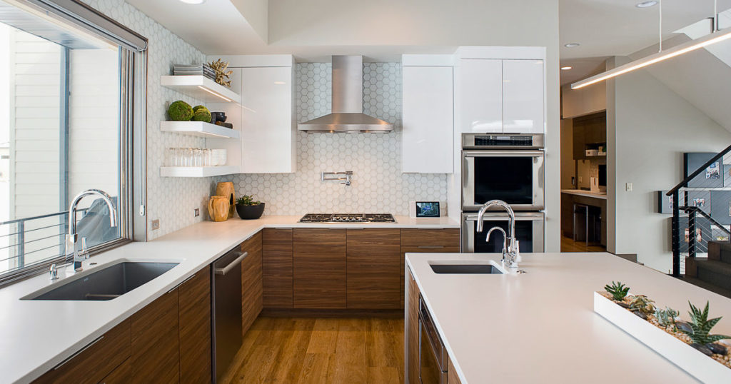 White modern kitchen with quartz countertops and floating shelves