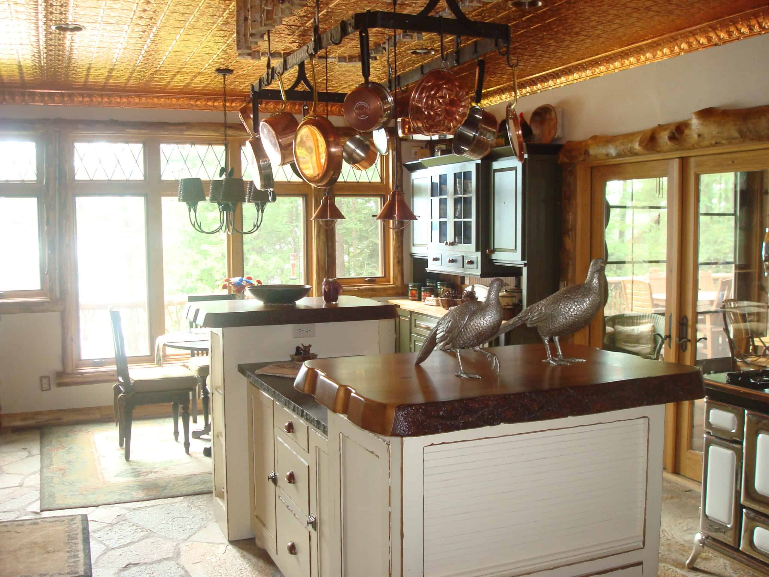 Rustic kitchen island shows distressed edges under live edge wooden tops and honed granite countertops