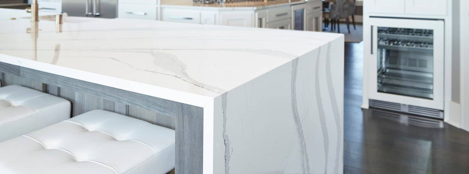white marble island with gray veins and waterfall edge by Cambria quartz